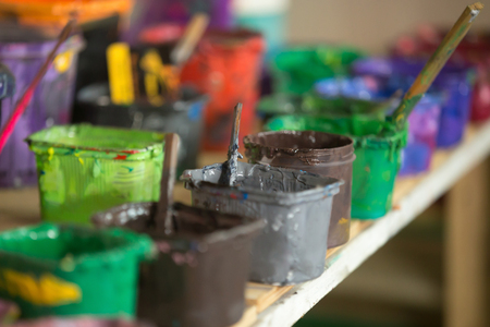 Close-up of silk screen printing ink collection on the shelf hold in plastic containers. Open cans with colorful paints in silkprinting professional workshop print house. Horizontal image