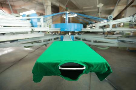Grünes T-Shirt mit Siebdruck-Maschine, schauen von der Mock-up T-Shirt vor Prozessdruck, horizontal Bild
