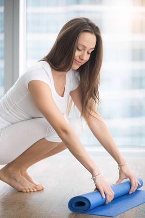 Young woman rolling, unrolling yoga, fitness mat after, before or after practice in a modern studio. Healthy lifestyle concept Stock Photo