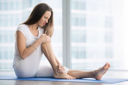 Unhappy young woman sitting on the mat, grabbing an ankle, unable to start yoga work out because of sport injury, feeling pain. Beginner doing wrong exercise without coacher Stock Photo