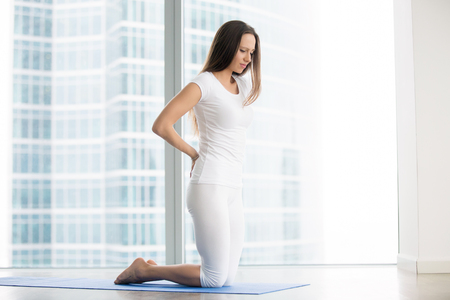 Young frustrated woman in studio trying to reduce stress, relieve aches and pains with yoga help, feeling backpain or unable to perform asanas, rehabilitation after spine trauma, beginner yoga fails Stock Photo