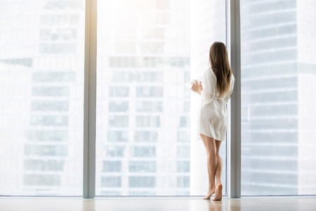 Young woman, wearing dress gown looking through floor window, waiting for a busy husband, dreaming of a job in big city, first day in unknown town, ready to conquer the capital. Rear view, full length Standard-Bild