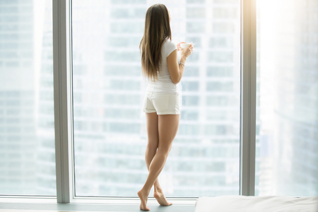 Full length portrait of young woman in casual home wear relaxing with cup of coffee in modern luxury apartment, with floor to ceiling window. Wakeup, dreaming, looking at rainy city scenery. Rear view