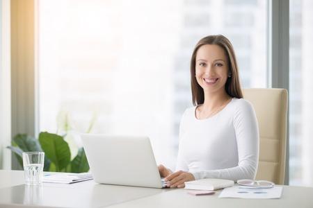 Recepcionista femenina sonriente joven en el escritorio de oficina moderno con una computadora portátil lista para saludar a clientes, clientes y visitantes, dirigirlos, consultas libres, primera impresión. Mirando la cámara Foto de archivo