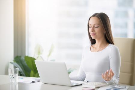 profesiones: Mujer joven cerca de la computadora portátil, practicar la meditación en el escritorio de oficina, delante del ordenador portátil, clases de yoga en línea, tomar un tiempo de descanso de un minuto, la curación de papeleo y la radiación portátil