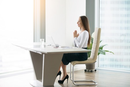 Young woman meditating at the modern office desk, finding a time in over-packed schedule, yoga as a habit and necessary requirement, preparing for a productive work, freedom of religion, of belief