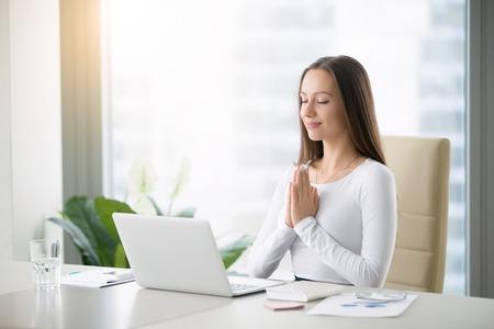 젊은 여성이 현대적인 사무실 책상에 앉아 명상, 일시 중지, 바쁜, 스트레스가 많은 사무실, 작업 과부하에 대한 치료, 한 순간 명상, 노트북 숭배 스톡 콘텐츠