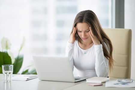 Jonge gefrustreerde vrouw die bij bureau voor laptop die lijden aan chronische dagelijkse hoofdpijn, behandeling online, de benoeming van een medische consultatie, elektromagnetische straling, loondoorbetaling bij ziekte Stockfoto