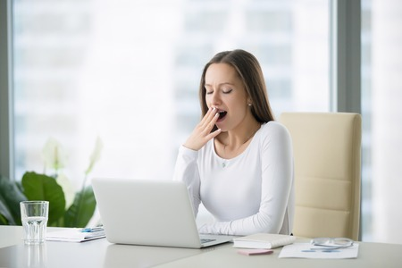 Young business woman yawning at a modern office desk in front of laptop, covering her mouth out of courtesy, chain reaction, drowsiness, unable to deal with boring job, monday after cool weekends Archivio Fotografico
