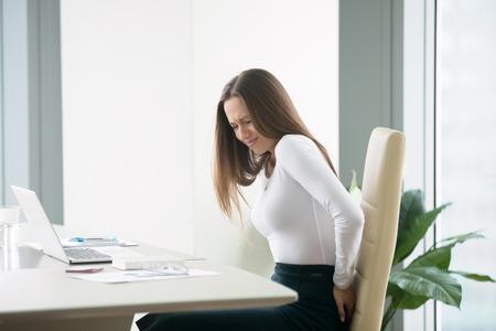 Profiel portret van een geïrriteerde jonge zakenvrouw op kantoor, haar rug moe voelen na het werken op laptop, ongemakkelijke stoel, gevoel van zware rugpijn, jeuk, moeite met zitten