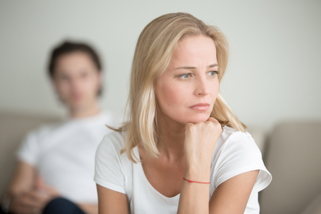 Serious sad woman thinking over a problem, man sitting aside, end of long-term relations, an alcoholic, drug addicted partner, poor conflict management skill, ongoing disagreements with adult son Zdjęcie Seryjne