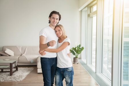 Portrait of young happy casual couple, holding a key, bought new apartment for family, newlyweds ready for fresh start, renting flat, housing market, low mortgage rate, cohabiting union, lottery win Stock Photo
