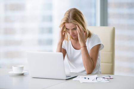 ラップトップに取り組んでいる近代的なオフィスのデスクでは、若い魅力的な女性マッサージ頭痛、偏頭痛、ストレス、慢性的な痛みの緩和を与え