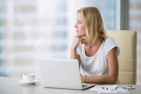 Mujer atractiva joven en un escritorio de oficina moderno, trabajando con la computadora portátil, mirando la ventana, pensando en una publicación, buscando inspiración, ayuda a ser productivo, actualización de la computadora Foto de archivo