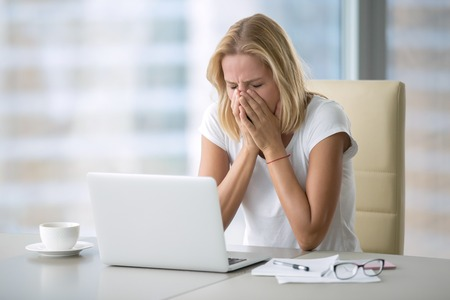Young attractive woman at a modern office desk, with laptop covering her face with palms because of sneezing, yawning, crying. Office manners, social skills, seasonal infection, sadness concept