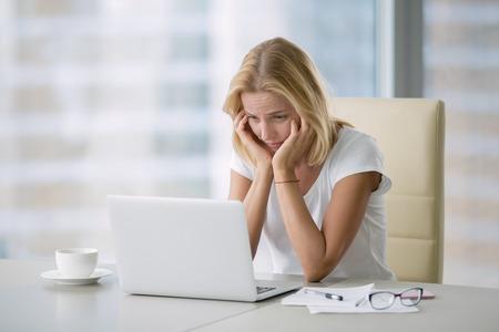 Portret van jonge aantrekkelijke vrouw vervelen op kantoor, met laptop, het gevoel hopeloos, verloren motivatie en inspiratie voor het project, niet bereid om te leren, Stockfoto