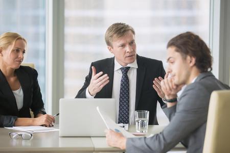 猛烈なボスお叱り若い不満のインターン悪い仕事の結果の。テーブルに座っている退去通知を受け取る効果がない会社員叫んでイライラ上司に耳を