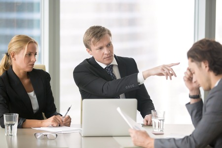 dismiss: Furious client scolding, firing incompetent contractor after unproductive work results. Young frustrated businessman receiving dismiss notification from his partner for incompetence