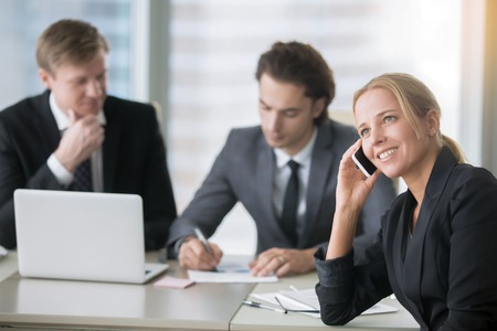 chatty: The group of businessmen working at the office desk woman demonstrating impolite office behavior, discussing private things in front of male colleagues, chatty lady, nonstop dialogue with a client