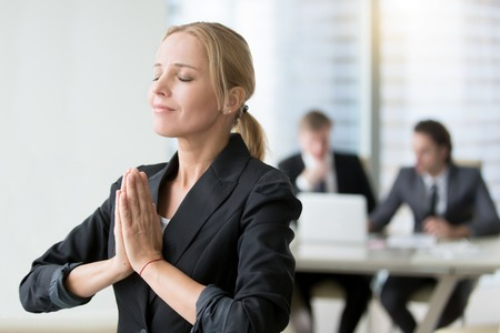 cherishing: Young businesswoman meditating, habits of successful woman, taking care of herself in personal and business life, staying present and cherishing all the good life. Relaxation techniques at workplace Stock Photo