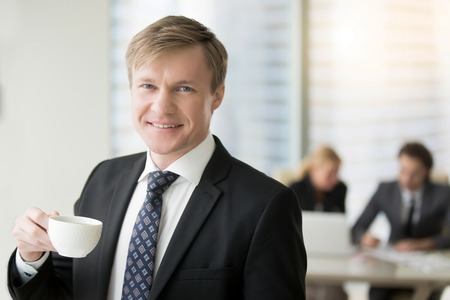 Portrait of young successful friendly smiling businessman looking at camera, relaxing after meeting with cup of coffee, creative entrepreneur, coffee break, having rest when others are working