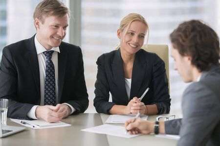 Businessman and businesswoman with tricky sweet smiles, a man unaware of bad intentions, signing a contract or agreeing to a partnership without fully reading through a business contract, hypnotized Stock Photo