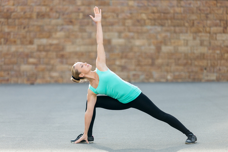 side angle pose: Sporty beautiful young woman practicing yoga, standing in Extended Side Angle exercise, Utthita parsvakonasana pose, working out, wearing sportswear, outdoor full length, brick wall background