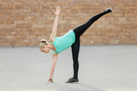 chandrasana: Sporty beautiful young woman practicing yoga, standing in Half Moon exercise, Ardha Chandrasana pose, working out, wearing sportswear, outdoor full length, brick wall background