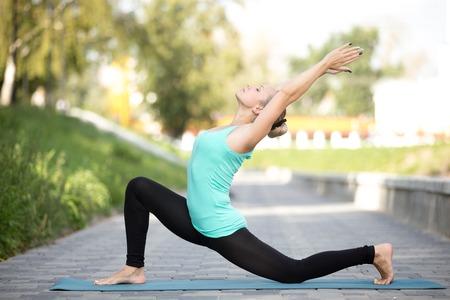 Sportief aantrekkelijk meisje beoefenen van yoga, die zich in ruiter van het paard oefening, anjaneyasana pose, het uitwerken, het dragen van sportkleding, openlucht volledige lengte, straat achtergrond, yoga mat op de stoep