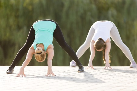 straddle: Two sporty attractive young women practicing yoga, standing in Wide Legged Forward Bend exercise, Prasarita Padottanasana pose, working out, wearing sportswear, outdoor full length, street background Stock Photo