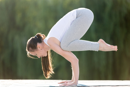 Sporty beautiful young woman practicing yoga, standing in Crane exercise, Bakasana pose, working out, wearing sportswear, outdoor full length, street or park summer background