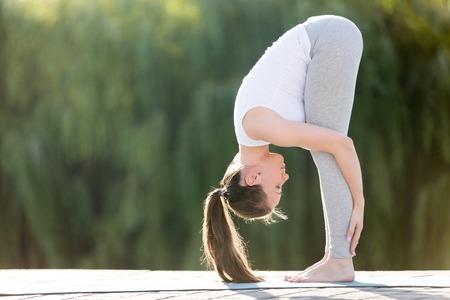 스포티 한 웃는 매력적인 젊은 여자 요가 연습, 서 앞으로 벤드, 머리 무릎 운동, uttanasana 포즈, 운동, 운동 전체 길이, 거리 배경을 입고 운동