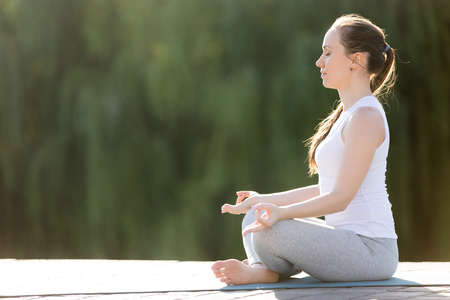 breathe easy: Sporty beautiful young woman practicing yoga, sitting in Easy Seat exercise, Sukhasana pose, working out, wearing sportswear, outdoor full length, park summer background. Copy space