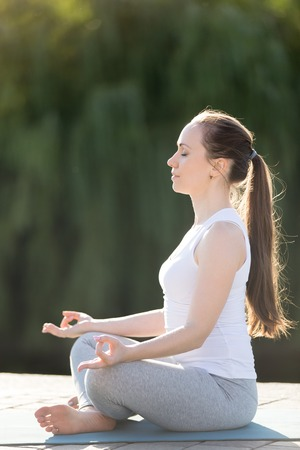 Portrait of a sporty beautiful young woman practicing yoga, sitting in Easy Seat exercise, Sukhasana pose, working out, wearing sportswear, outdoor full length, park background, summer day Stock Photo