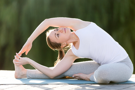 janu: Sporty young woman practicing yoga, sitting in Revolved Head to Knee Forward Bend exercise, Parivrtta Janu Sirsasana pose, working out, wearing sportswear, outdoor, sunny summer day background