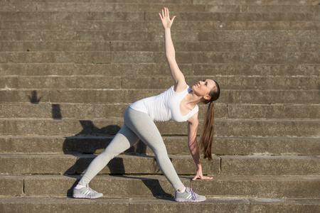 revolved: Sporty attractive happy young woman practicing yoga, standing in Revolved Triangle exercise, Parivrrta Trikonasana pose, working out, wearing sportswear, outdoor, stone stair background with a shadow Stock Photo