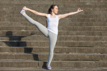 hasta: Sporty attractive young woman practicing yoga, standing in Extended Hand to Big Toe exercise, Utthita Hasta Padangustasana pose, working out, wearing sportswear, outdoor, stone stair background