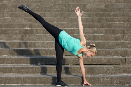 chandrasana: Sporty attractive young woman practicing yoga, standing in Half Moon exercise, Ardha Chandrasana pose, working out, wearing sportswear, outdoor, urban stone stair background. full length