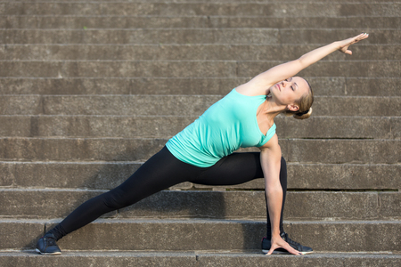side angle pose: Sporty attractive young woman practicing yoga, standing in Extended Side Angle exercise, Utthita parsvakonasana pose, working out, wearing sportswear, outdoor, urban stone stair background