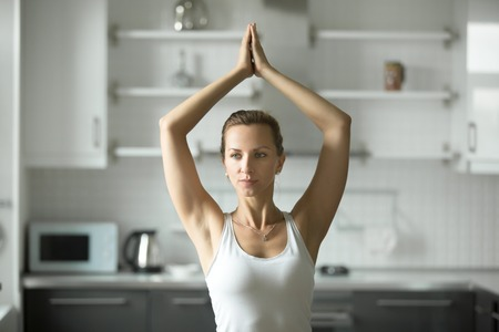 vriksasana: Portrait of attractive woman practicing yoga at home in the morning, standing in yoga pose, working out, doing sun salutation exercises, wearing white sportswear, indoor, home interior background