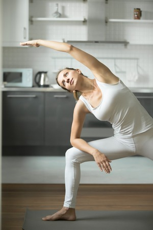 side angle pose: Happy sporty attractive young woman practicing yoga, standing in Extended Side Angle exercise, Utthita parsvakonasana pose, working out, wearing white sportswear, indoor, home interior background