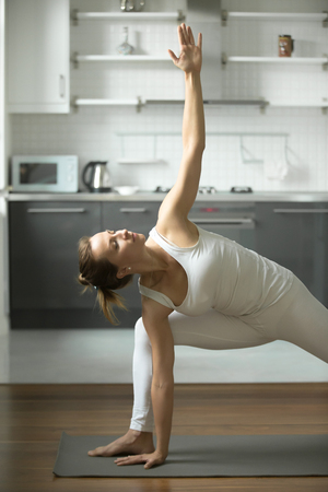 side angle pose: Beautiful Sporty young woman practicing yoga, standing in Extended Side Angle exercise, Utthita parsvakonasana pose, working out, wearing white sportswear, indoor, home interior background Stock Photo