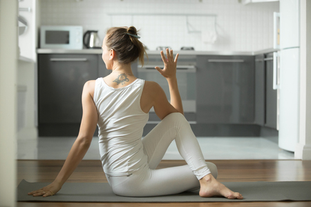 ardha: Sporty young woman practicing yoga, sitting in Half lord of the fishes exercise, Ardha Matsyendrasana pose, working out, wearing white sportswear, indoor full length, home interior background