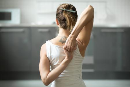 Cerca de las manos femeninas detrás de la espalda, mujer practicando yoga, sentado en el ejercicio Cow Face, pose de Gomukasana, trabajando, vistiendo ropa deportiva blanca, interior, fondo interior casero Foto de archivo