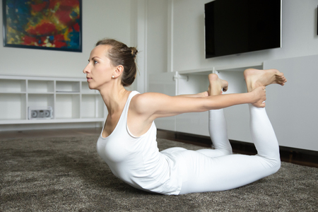 dhanurasana: Sporty attractive young yogi woman practicing yoga, stretching in Bow exercise, Dhanurasana pose, working out, wearing white sportswear, indoor full length, home interior background