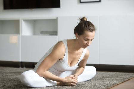 Portrait of young woman practicing yoga, sitting in Butterfly exercise, baddha konasana pose, working out, wearing white sportswear, indoor full length, home interior background