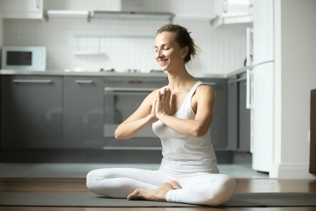 siddhasana: Sporty smiling attractive woman practicing yoga, sitting in Half Lotus exercise, Siddhasana pose, working out, wearing white sportswear, indoor full length, home interior background