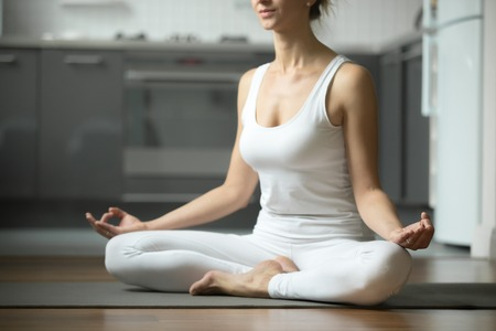 ardha: Sporty attractive woman practicing yoga, sitting in Half Lotus exercise, Siddhasana pose, working out, wearing white sportswear, indoor, home interior background. Midsection close up