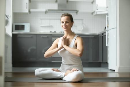 siddhasana: Sporty attractive woman practicing yoga, sitting in Lotus exercise, Padmasana pose, working out, wearing white sportswear, indoor full length, home interior background, smiling looking at the camera Stock Photo