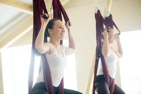 Two young yogi women doing aerial yoga practice in purple hammocks in fitness club. Beautiful females working out, performing aero yoga in class. Variation of baddha konasana, cobbler, butterfly pose Stock Photo